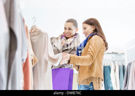 Young female friends choosing sweater in store - Stock Photo