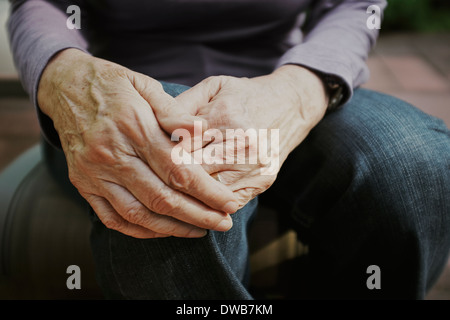 Cropped shot of senior woman with hands on knee - Stock Photo