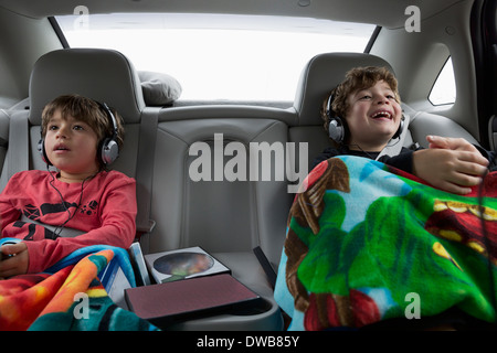 Brothers in back seat of car, wearing headphones - Stock Photo