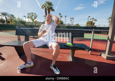 Tired senior tennis player relaxing on bench at court - Stock Photo