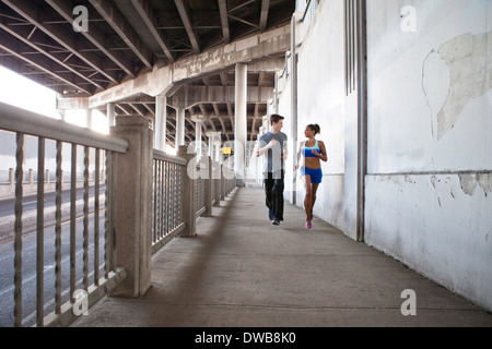 Young couple running on city bridge - Stock Photo