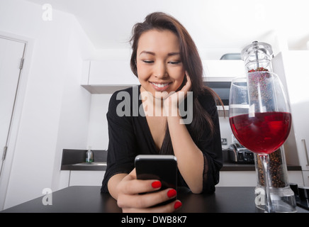 Beautiful young woman reading text message on smart phone at kitchen counter - Stock Photo