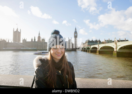 Portrait of beautiful young woman standing by river Thames, London, UK - Stock Photo