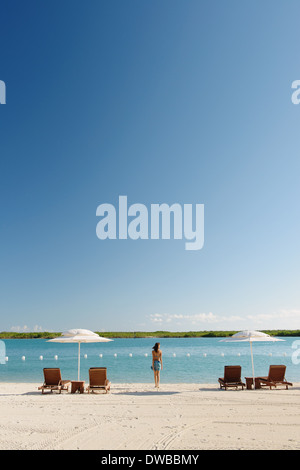Solitary young woman on beach, Providenciales, Turks and Caicos Islands, Caribbean - Stock Photo