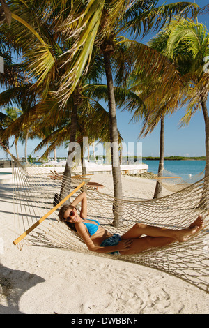 Young woman reclining in hammock, Providenciales, Turks and Caicos Islands, Caribbean - Stock Photo