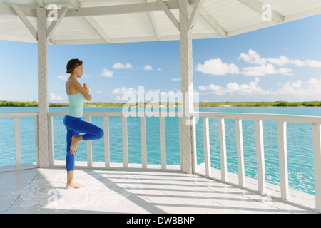 Young woman doing yoga in coastal gazebo, Providenciales, Turks and Caicos Islands, Caribbean - Stock Photo
