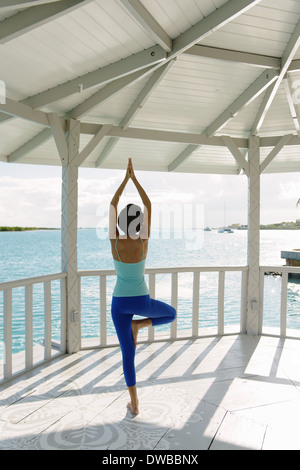 Young woman practicing yoga tree pose in coastal gazebo, Providenciales, Turks and Caicos Islands, Caribbean - Stock Photo