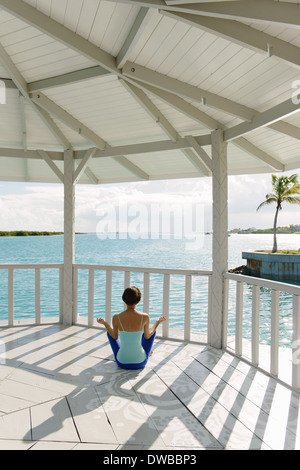 Young woman practicing yoga lotus pose in coastal gazebo, Providenciales, Turks and Caicos Islands, Caribbean - Stock Photo