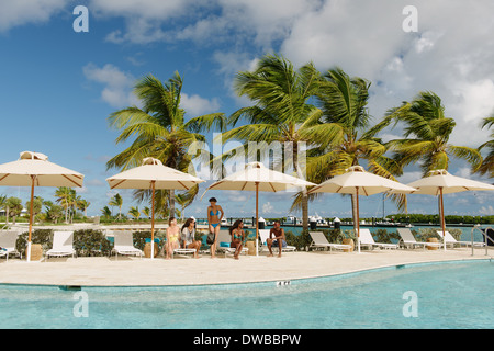 Group of young adults sunbathing by the pool, Providenciales, Turks and Caicos Islands, Caribbean - Stock Photo