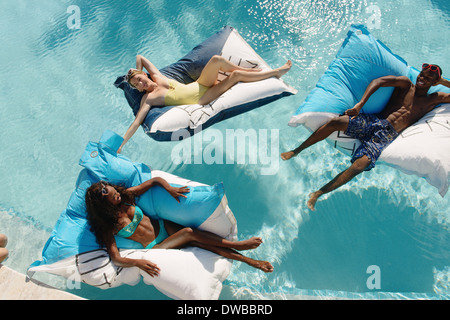 Three young adults reclining on airbeds in swimming pool, Providenciales, Turks and Caicos Islands, Caribbean - Stock Photo