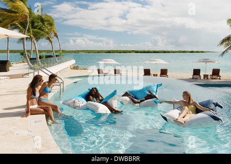 Group of young adults relaxing in swimming pool, Providenciales, Turks and Caicos Islands, Caribbean - Stock Photo