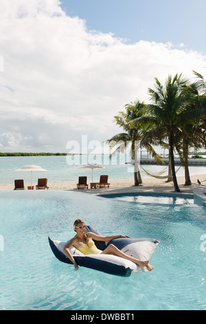 Young woman reclining on airbed in swimming pool, Providenciales, Turks and Caicos Islands, Caribbean - Stock Photo