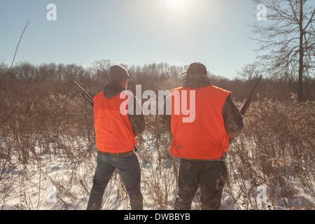 Mid adult man and teenage son hunting in Petersburg State Game Area, Michigan, USA - Stock Photo