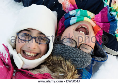 Boy and girl wearing winter hats and glasses, laughing - Stock Photo