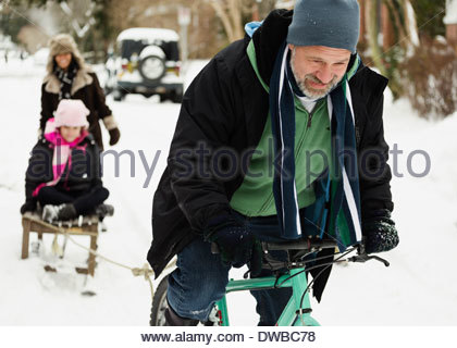 Parents and daughter playing with toboggan in snow - Stock Photo
