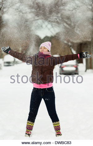 Teenage girl throwing powdered snow mid air in street - Stock Photo