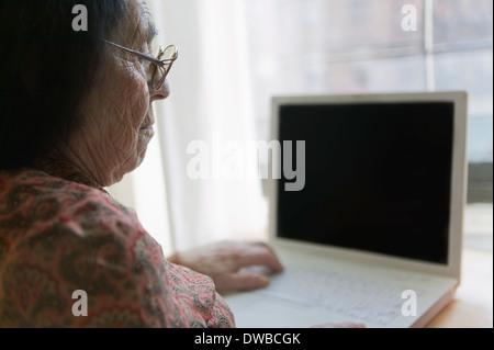 Senior woman using laptop - Stock Photo
