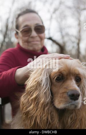 Senior woman patting dog - Stock Photo