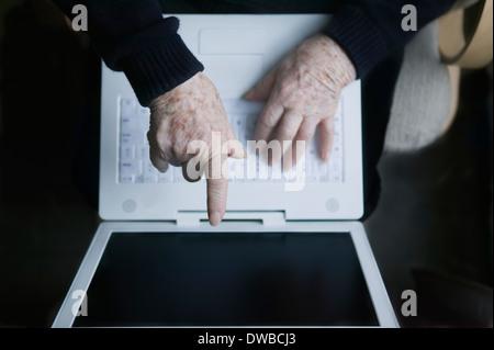 Senior woman pointing at laptop screen - Stock Photo
