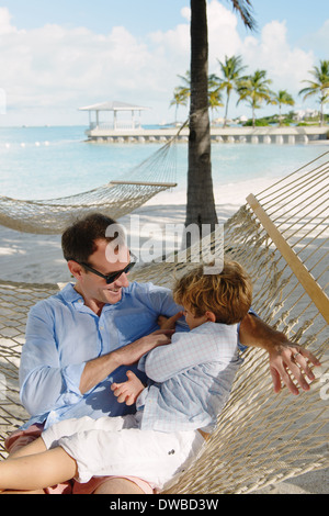 Father and son relaxing in beach hammock, Providenciales, Turks and Caicos Islands, Caribbean - Stock Photo