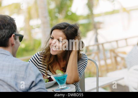 Couple enjoying meal with cocktails in resort restaurant, Providenciales, Turks and Caicos Islands, Caribbean - Stock Photo