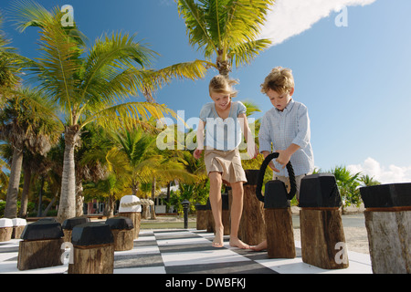 Brother and sister playing giant chess, Providenciales, Turks and Caicos Islands, Caribbean - Stock Photo
