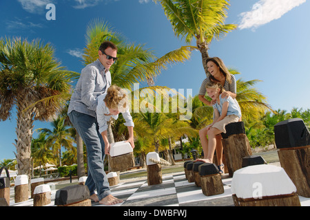 Family playing giant chess, Providenciales, Turks and Caicos Islands, Caribbean - Stock Photo