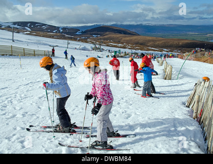 Children having skiing lessons on nursery slopes at Cairngorm Mountain Ski Centre, by Aviemore, Scottish Highlands, - Stock Photo