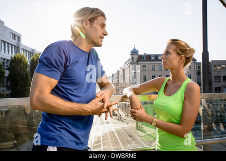Two adult runners taking a break on city footbridge - Stock Photo