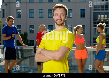 Young male trainer and class taking a break on city rooftop - Stock Photo