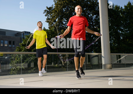 Two male athletes training with skipping ropes - Stock Photo