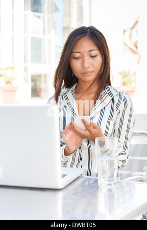 Asian girl text messaging on smart phone in front of her laptop - Stock Photo