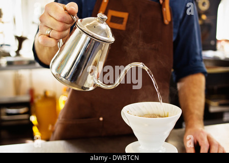 Close up of barista pouring boiling water into coffee filter - Stock Photo