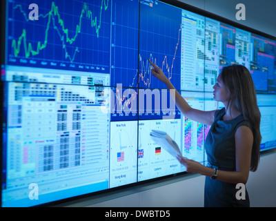 Businesswoman preparing presentation on graphical screens - Stock Photo