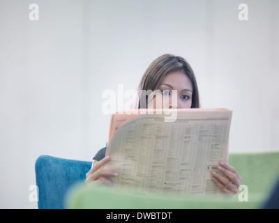 Businesswoman reading British newspaper - Stock Photo
