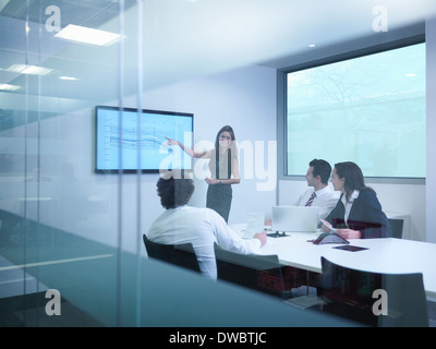 View through glass wall of business colleagues using screen in meeting - Stock Photo