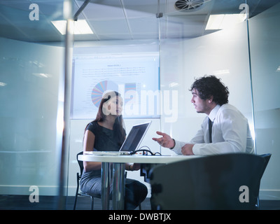 View through glass windows of meeting room of business colleagues in discussion - Stock Photo