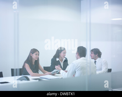 View through glass wall of business colleagues in meeting - Stock Photo