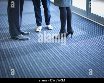 Business colleagues in meeting in office foyer, low section