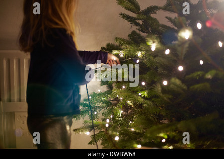 Young girl pulling at christmas lights - Stock Photo