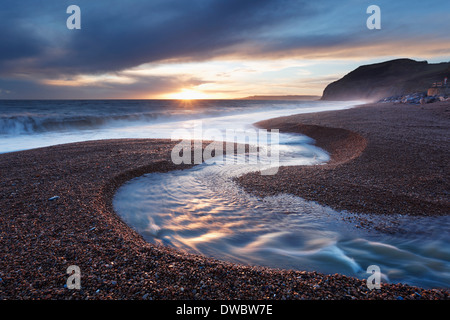 River Winniford flowing into the sea at Seatown Beach with the cliffs of Golden Cap in the Distance. Jurassic Coast. - Stock Photo