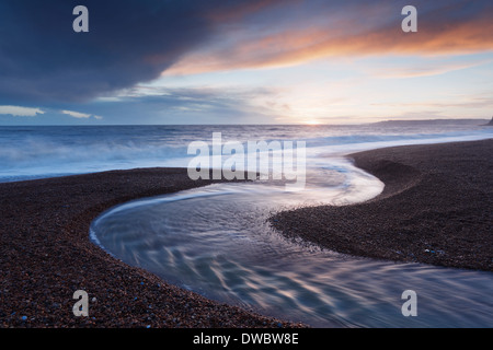 River Winniford flowing into the sea at Seatown Beach. Jurassic Coast World Heritage Site. Dorset. UK. - Stock Photo