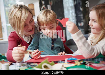 Mother and two children drawing at kitchen table - Stock Photo