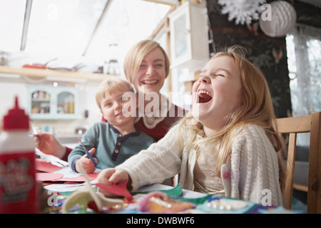 Mother and two children craft making at kitchen table - Stock Photo