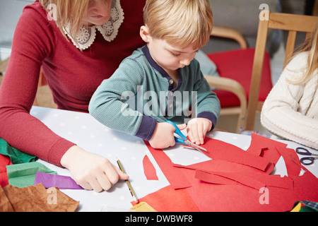 Mother and son craft making at kitchen table - Stock Photo