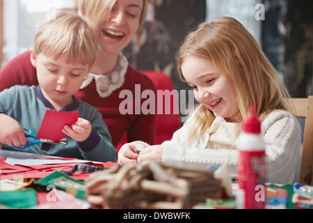 Mother and two children crafting at kitchen table - Stock Photo
