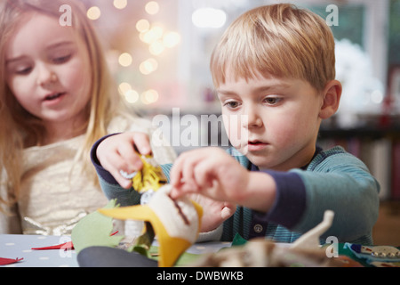 Young brother and sister crafting at kitchen table - Stock Photo