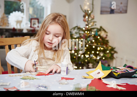Young girl cutting out paper preparing for christmas - Stock Photo