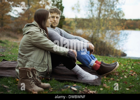 Young couple in winter clothing sitting on blanket while camping - Stock Photo