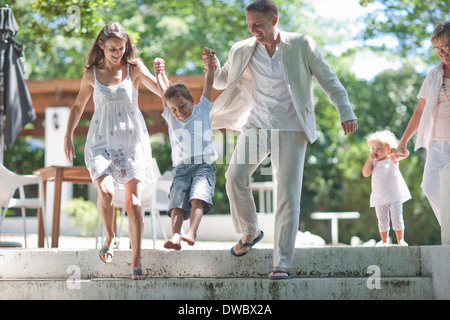 Parents lifting son over steps - Stock Photo
